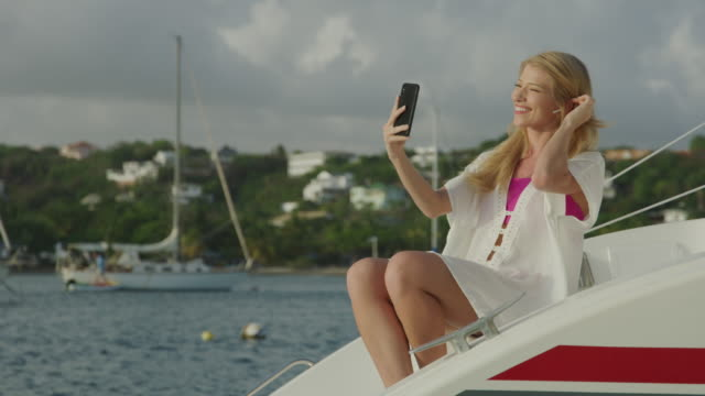 smiling woman on catamaran video chatting on cell phone / prickley bay, grenada - one young woman only stock videos & royalty-free footage