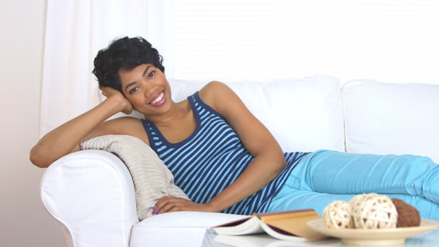 smiling woman on couch - one mid adult woman only stock videos & royalty-free footage
