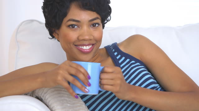 smiling woman on couch with mug of coffee - one mid adult woman only stock videos & royalty-free footage