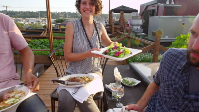MS TS Smiling woman passing plate of food during dinner with friends in rooftop garden on summer evening