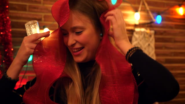 cu smiling woman posing while wearing large ribbon during holiday party with friends - front view stock videos & royalty-free footage