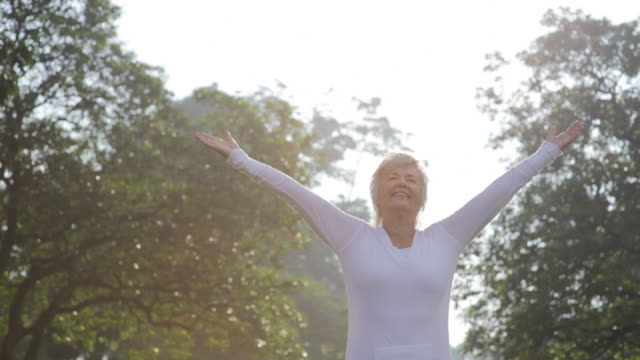A smiling woman practices yoga outdoors.