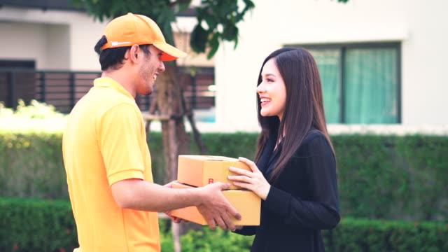 vídeos y material grabado en eventos de stock de sonriente mujer recibe paquete postal después de la firma electrónica firma dispositivo permanente en el jardín - haz de luz