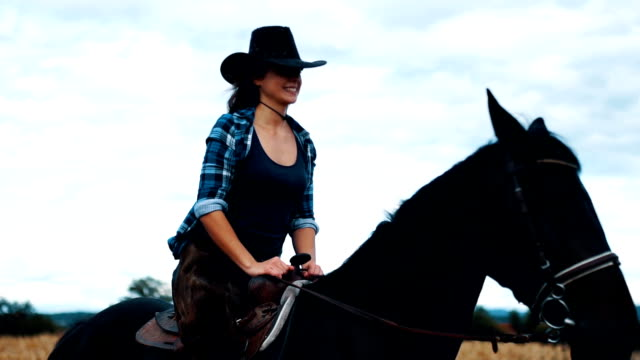 Smiling woman riding a black horse on the farm