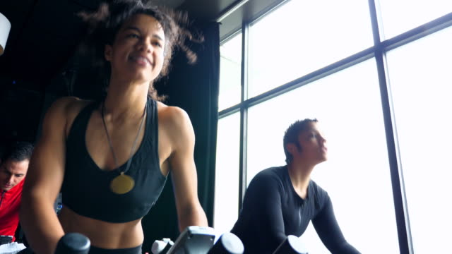 MS Smiling woman riding indoor bike during cycling class with friends
