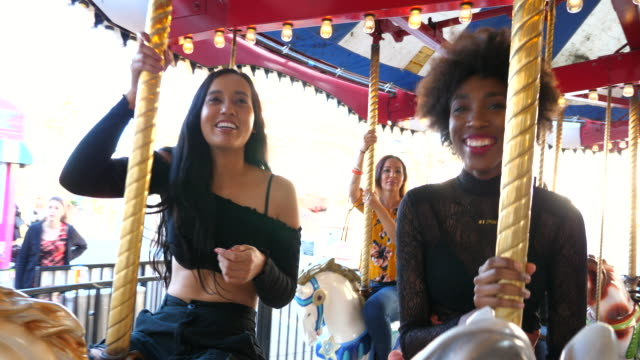 vídeos de stock, filmes e b-roll de ms smiling woman riding merry go round in amusement park - 30 34 anos