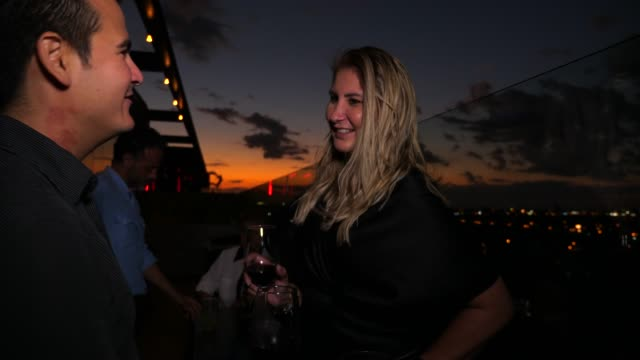 ms smiling woman sharing drinks with boyfriend at rooftop bar at sunset - flirting stock videos & royalty-free footage