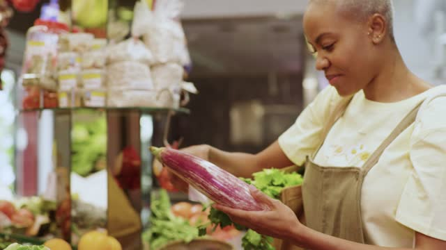 smiling woman shopping a fresh eggplant at a market stand - freshness stock videos & royalty-free footage