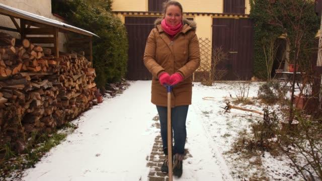 smiling woman shoveling snow. - 30代点の映像素材/bロール