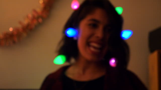 r/f cu smiling woman singing and dancing while wearing holiday light necklace during holiday party - real people stock videos & royalty-free footage