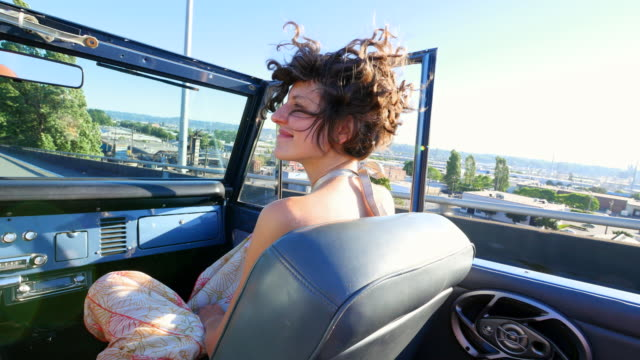 ms smiling woman sitting in passenger seat of convertible with boyfriend driving on city overpass - サンドレス点の映像素材/bロール