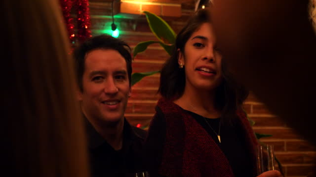 ms smiling woman sitting on boyfriends lap while hanging out with friends during holiday party - grace stock videos & royalty-free footage