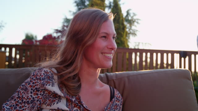 vidéos et rushes de ms smiling woman sitting on couch in backyard of home during neighborhood party on summer evening - adulte d'âge moyen