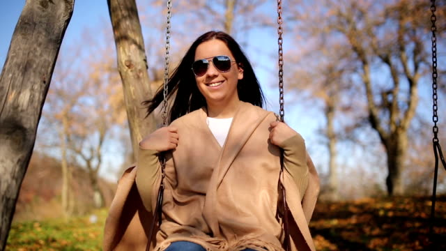 smiling woman sitting on swing in park - fine art portrait stock videos & royalty-free footage