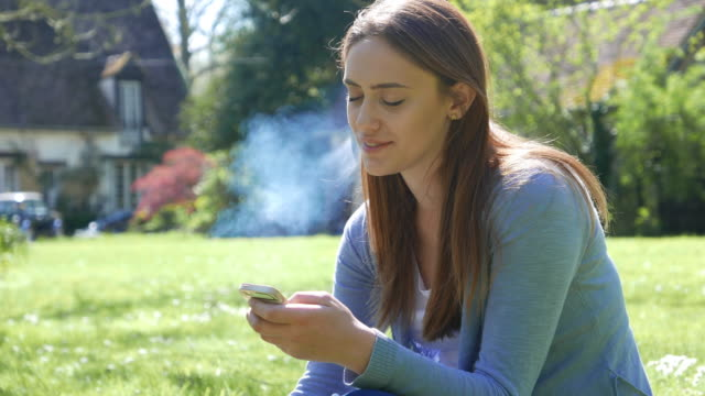 smiling woman sitting on the grass and texting - cigarette stock videos & royalty-free footage