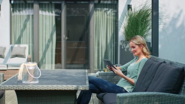 donna sorridente seduta con tablet digitale nel patio - capelli biondi video stock e b–roll