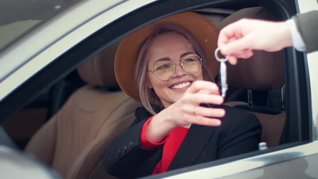 smiling woman taking keys to her new car - giving stock videos & royalty-free footage