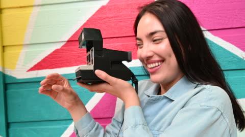 vídeos y material grabado en eventos de stock de smiling woman taking photograph with instant camera by colorful mural - transferencia de impresión instantánea
