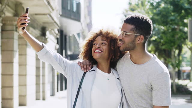 smiling woman taking selfie with man in city - city break stock videos & royalty-free footage