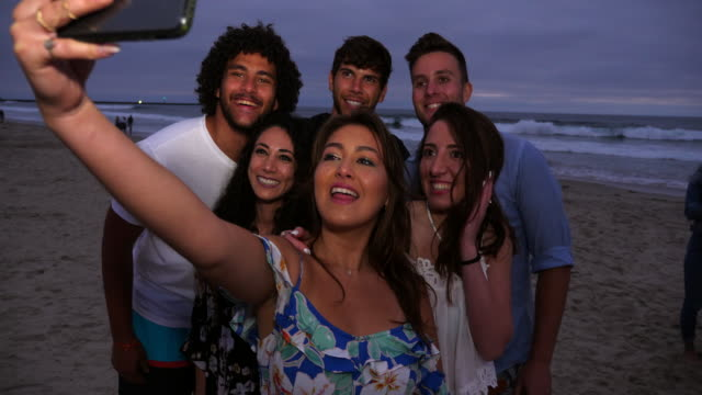 ms smiling woman taking selfie with smart phone and friends during beach party on summer evening - 20 29 years stock videos & royalty-free footage