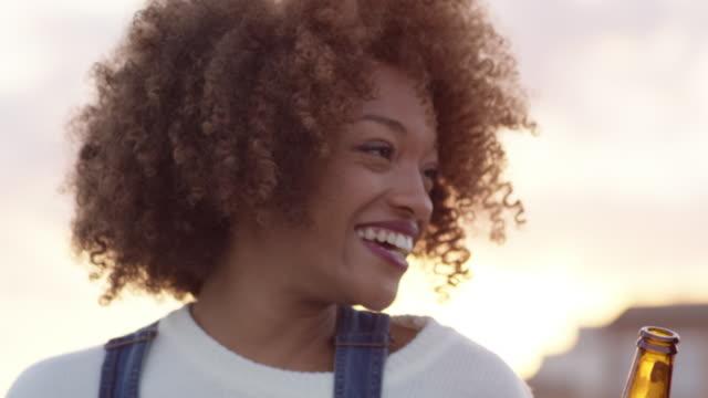 lächelnde frau im gespräch mit freund auf dach - langes haar stock-videos und b-roll-filmmaterial