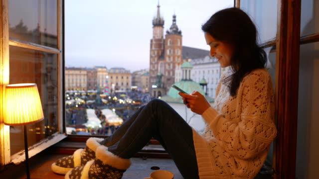 vídeos de stock, filmes e b-roll de mensagens de mulher sorridente no peitoril da janela - peitoril de janela