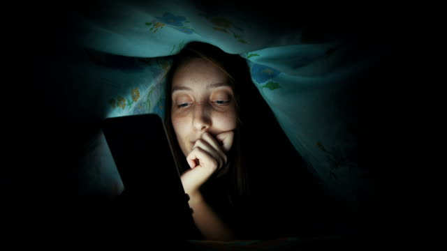 smiling woman texting under blanket - bed sheets stock videos & royalty-free footage