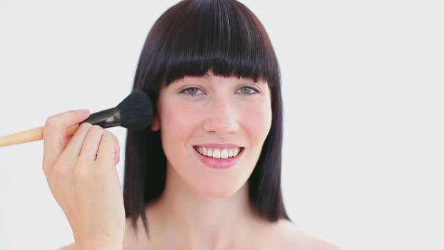 Smiling woman using a powder brush