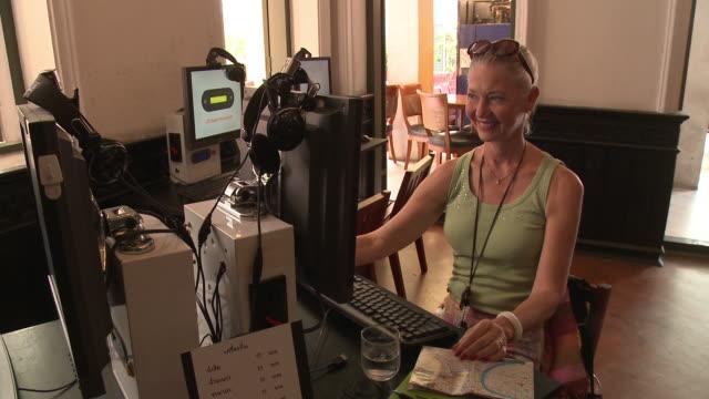 MS Smiling woman using computer in internet cafe, Bangkok, Thailand