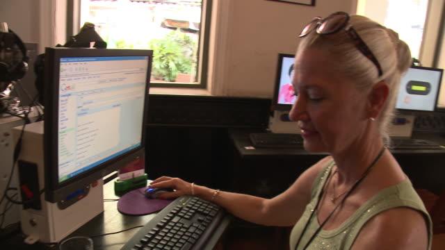 MS TD Smiling woman using computer in internet cafe, Bangkok, Thailand
