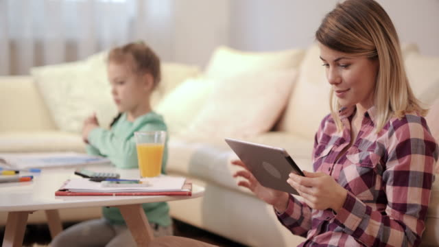 smiling woman using digital tablet with her daughter in the background. - touchpad stock videos & royalty-free footage