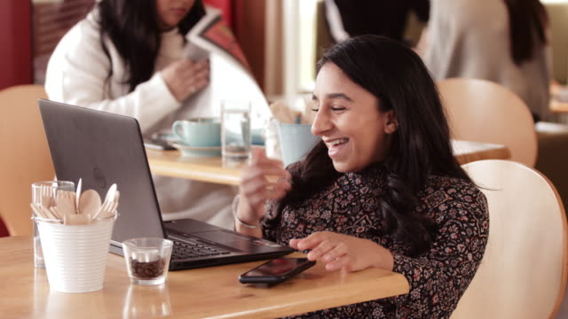 smiling woman using laptop in cafe - less than 10 seconds stock videos & royalty-free footage