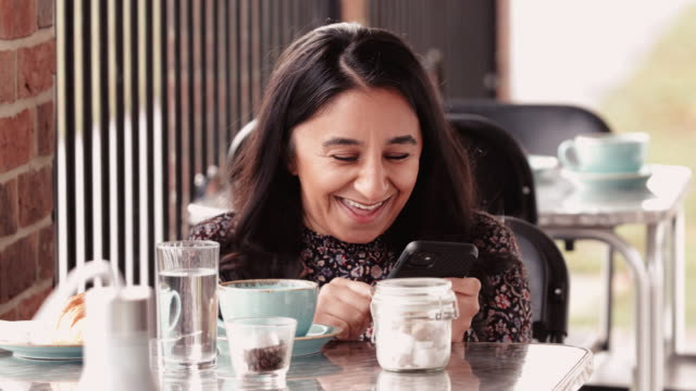 smiling woman using smartphone in cafe - andersfähigkeiten stock-videos und b-roll-filmmaterial