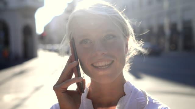 vídeos de stock e filmes b-roll de smiling woman using smartphone in the street. - independência