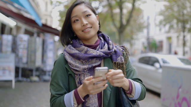 smiling woman using smartphone on footpath in city - footpath stock videos & royalty-free footage
