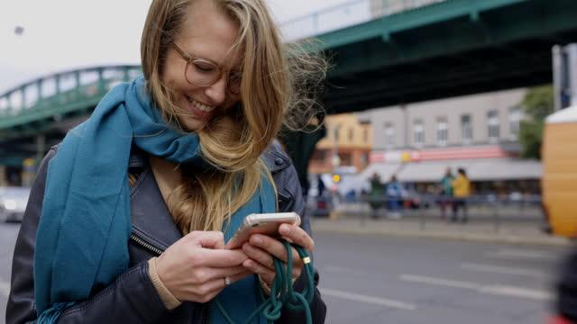 vidéos et rushes de femme de sourire utilisant le smartphone sur la rue dans la ville - activité