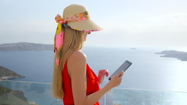 Leende kvinna använder pekplattan i Santorini