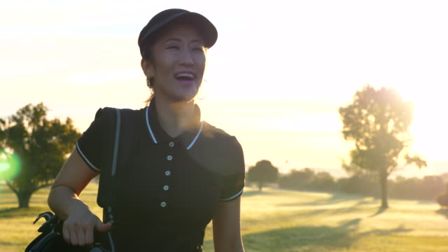 ms ts smiling woman walking on fairway while playing early morning round of golf with mother - korean ethnicity stock videos & royalty-free footage