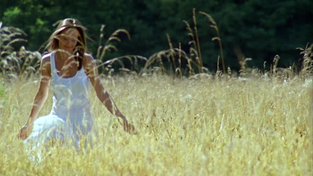 ms, smiling woman walking through grass in meadow, saint ferme, gironde, france - maglietta senza maniche video stock e b–roll