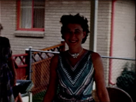 a smiling woman walks across a back porch. - 1957年点の映像素材/bロール