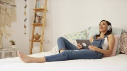 Smiling woman watching video on digital tablet