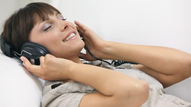 donna sorridente indossando cuffie - cantare video stock e b–roll