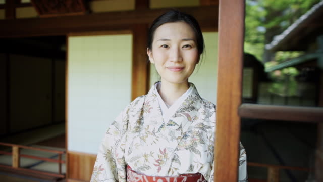 smiling woman wearing kimono poses for camera - kimono stock videos & royalty-free footage