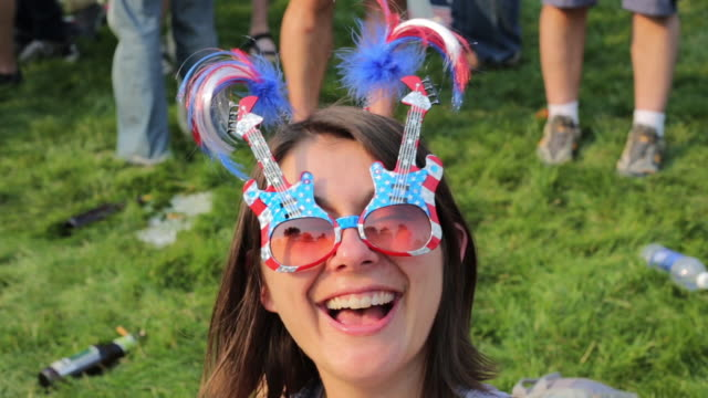 smiling woman wears american flag and guitar sunglasses as hundreds of grateful dead fans hang out on a lawn south of soldier field. the grateful... - fare video stock e b–roll