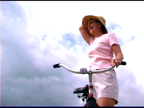 smiling woman with bicycle outdoors - only mature women stock videos & royalty-free footage