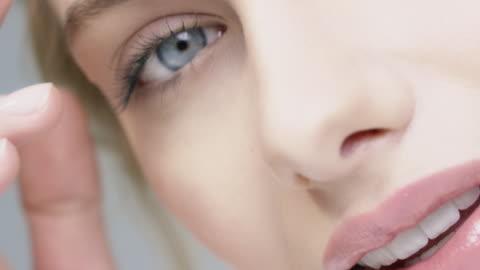 vídeos y material grabado en eventos de stock de mujer sonriente con ojos azules, tocar su piel - mujer bella