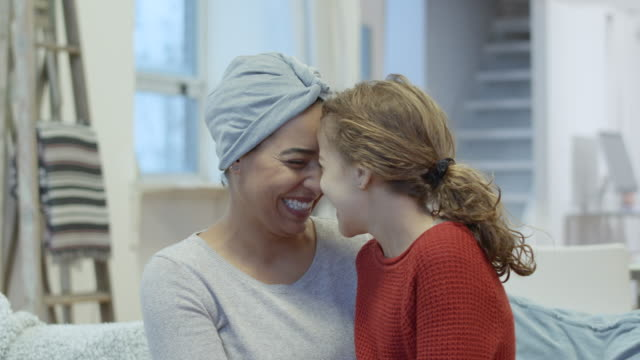 smiling woman with cancer embraces her daughter - positive emotion stock videos & royalty-free footage