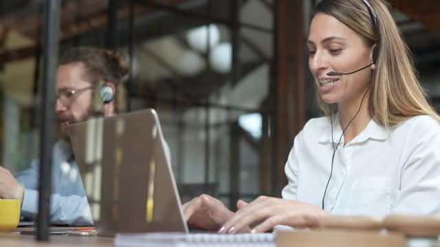 lächelnde frau mit laptop und kopfhörer im gespräch mit einem kunden - telefonist stock-videos und b-roll-filmmaterial