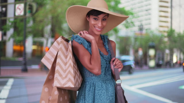 Smiling woman with shopping bags over her shoulder wearing in San Francisco city