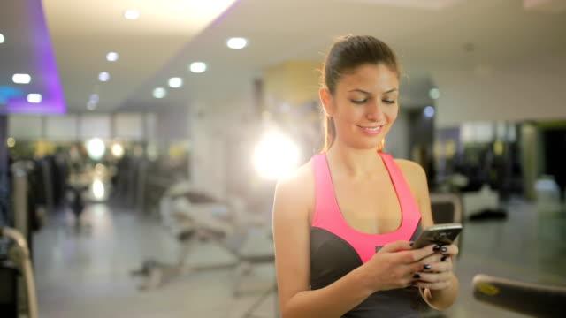 vídeos de stock, filmes e b-roll de mulher sorridente com o smartphone em treademill - a caminho